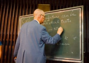 W. Edwards Deming writing on chalkboard (about statistical testing) - 1980s